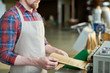 Mid section of unrecognizable man wearing apron packing freshly roasted coffee beans in craft paper bags while working in artisan roastery house, copy space
