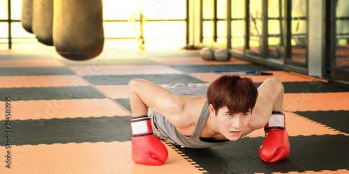 Men put on red Boxing Gloves push up in the gym.