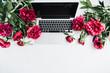 Leinwandbild Motiv Minimal workspace with laptop and pink peony flowers on white background. Flat lay, top view blog hero header.