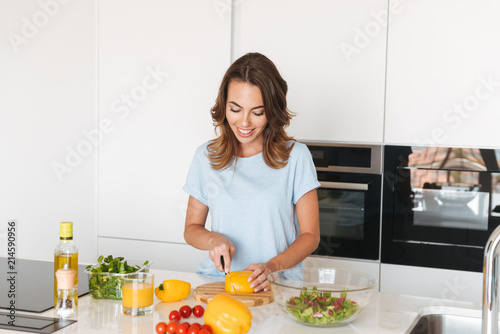 Foto Murales Smiling young girl making healthy lunch
