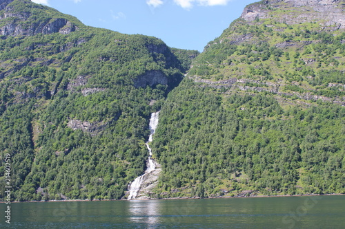 Foto Spatwand Olijf Waterfall ending in Geirangerfjord, Norway
