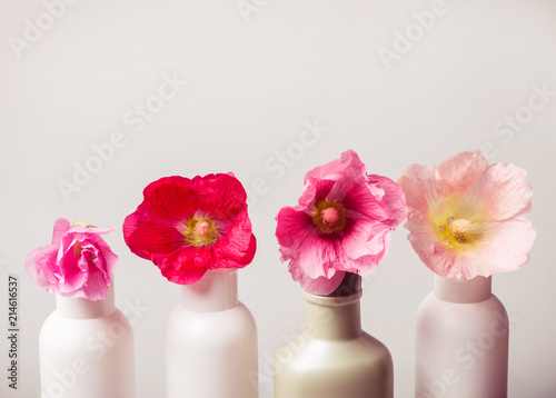 Natural Cosmetics set and flowers on gray background