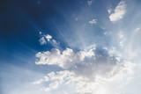 Sonnenstrahlen und Wolken am Himmel - 214634719
