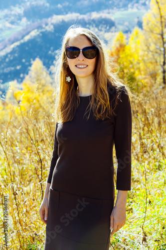 Plexiglas Geel girl colorful autumn forest high mountains carpathians landscape enjoy view perspective sunglasses brown dress sunlight yellow sky blue