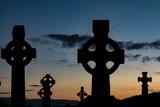 Celtic cross Cemetery gravestones ,silhouette dusk sky background