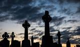 Cemetery celtic cross gravestones silhouette dusk sky background