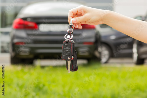 Hand Of A Girl With A Car Key In Her Hand Against A New Car