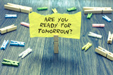 Handwriting text Are You Ready For Tomorrow question. Concept meaning Preparation to the future Motivation Paperclip hold written torn page many clips laid on bluish wooden floor. - 214673718
