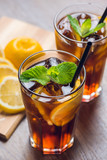 Traditional ice tea, chilled, with lemon, mint and ice on rustic table