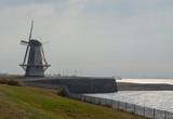 Tourist destination, traditional Dutch windmill on sea shore, Vl