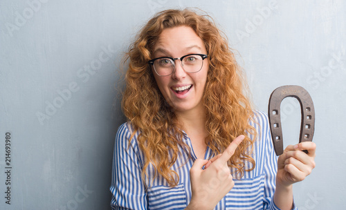 Leinwandbild Motiv Young redhead woman over grey grunge wall holding horseshoe very happy pointing with hand and finger