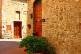 A picture of a house and flowers in front of the door in one of the narrow streets of San Gemigniano