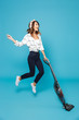 Full length photo of funny housewife 20s listening to music via wireless headphones and jumping with vacuum cleaner, isolated over blue background