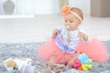 Baby dressed in tutu playing on rug
