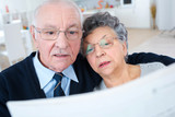 senior couple reading newspaper together at home - 214731938