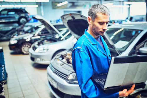 Fototapeta mechanic man with automotive diagnostic scanner and clipboard checking car system at workshop