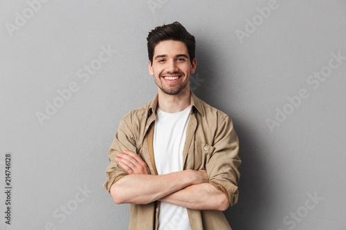 Leinwandbild Motiv Portrait of a happy young casual man standing