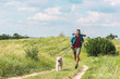 Quadro traveler running with dog on path on summer meadow
