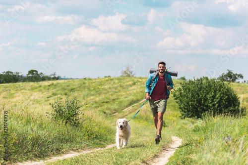 Leinwandbild Motiv traveler running with dog on path on summer meadow