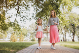 Walking with mother. Cute beautiful girl wearing short pink skirt with lollipop in her hand walking with mother - 214750314