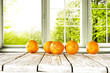 Fresh orange fruits on white wooden table and free space for your bottle or glass. Window background with summer garden landscape.