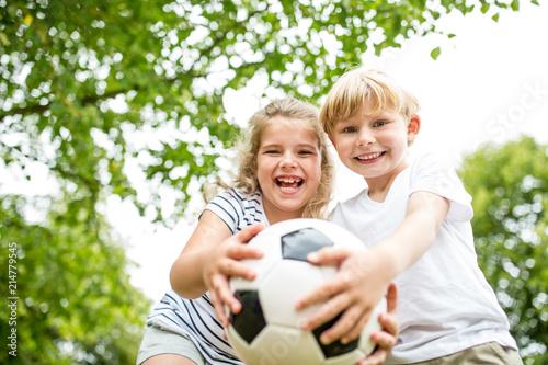 Geschwister spielen mit einem Fußball