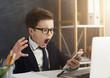Leinwandbild Motiv Emotional business boy screaming at smartphone