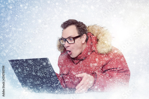 Foto Murales Man in glasses and red winter clothes with laptop, cold, snow.