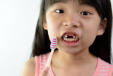 Little Asian girl without front teeth holding a tooth brush - 214781555