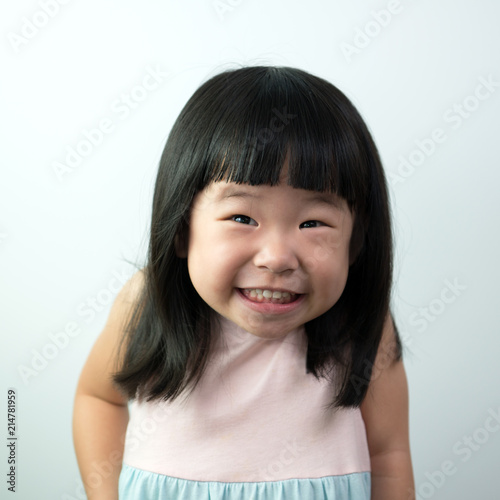 Leinwandbild Motiv Happy little asian girl with funny face isolated on white background