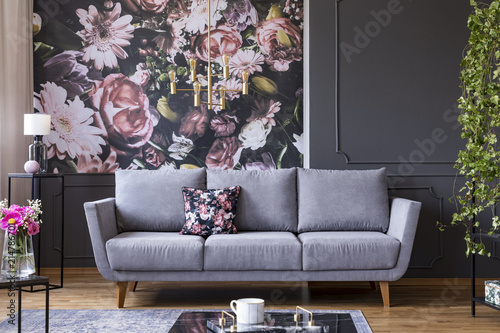 Grey lounge with patterned cushion in real photo of dark living room interior with floral wallpaper, molding on wall and gold lamp - 214786701
