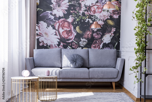 Real photo of bright sitting room interior with floral wallpaper, grey lounge with cushion, gold end tables and window with drapes