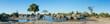 Leinwandbild Motiv A colour, panorama image of a herd of elephants, Loxodonta africana, bathing and drinking at a dwindling waterhole in Savute, Botswana.