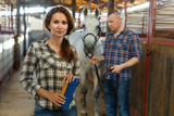 Couple cleaning horse while standing at  stabling indoor - 214805119