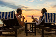 Leinwanddruck Bild - Rear view of a young romantic couple in love sitting on wooden chairs, while drinking cocktails on a tropical beach at sunset during vacation or honeymoon in Indonesia