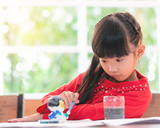 Chinese girl is painting on a doll in classroom