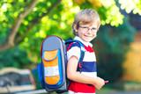 little kid boy with school satchel on first day to school - 214820364