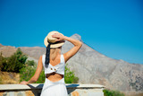 Back side view at girl in hat and white dress standing on balcony with mountain on background. Crete, Greece