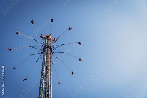 Aluminium Amusementspark Chairoplane carousel up in the blue cloudless sky