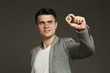 portrait of a young guy in a jacket with a bitcoin coin in his hand on a gray background