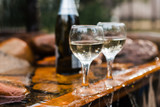 Love, romance, holiday, celebration concept. Bottle and glasses of champagne chilled by waterfall in summer forest on sunset. - 214832789