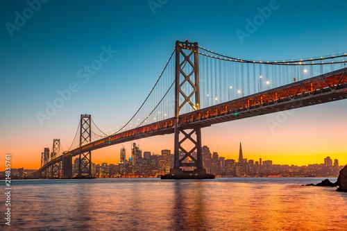 Leinwanddruck Bild San Francisco skyline with Bay Bridge at sunset, California, USA