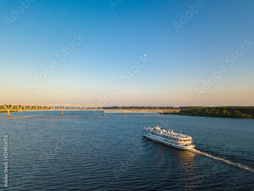Canvas Blauw Aerial view white cruise ship on river Volga with railroad bridge on background. Cruise ship near Kostroma city at sunset.