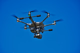 Large Security Surveillance Drone Flying  in a Blue Sky - Unmanned Surveillance Drone in a Summer Sky - Emergency Services, Search and Rescue - Mapping - Surveillance - 214857701