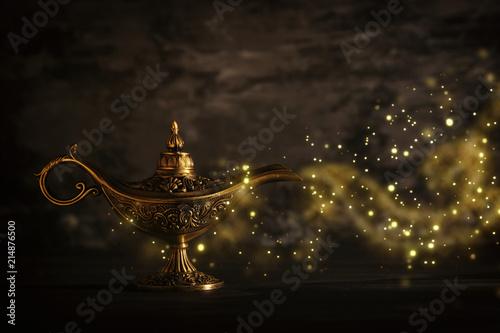 Leinwandbild Motiv Image of magical mysterious aladdin lamp with glitter sparkle smoke over black background. Lamp of wishes.