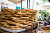 Tray full of Greek traditional round sesame bread rings, displayed in a street market with bokeh background