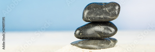 Plexiglas Zen Stenen Three black stones in the sand, blue sky background, square