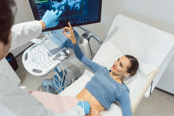 Doctor gynecologist and woman in ultrasonic pregnancy test at fertility clinic