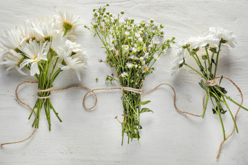 Bouquets of beautiful camomile flowers on white wooden background