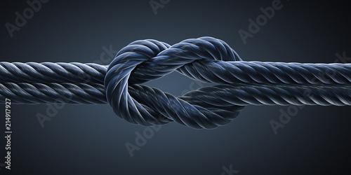 Leinwandbild Motiv Schwarzer Kreuzknoten vor dunklem Hintergrund